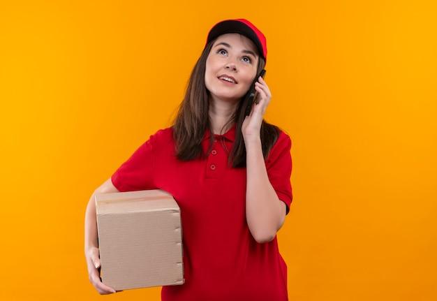 Glimlachende jonge leveringsvrouw die rode t-shirt in rode glb draagt die een doos houdt en een telefoongesprek voert op geïsoleerde oranje muur