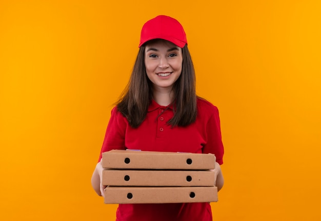 Glimlachende jonge leveringsvrouw die rode t-shirt in rode glb draagt die een pizzadoos op geïsoleerde oranje muur houdt