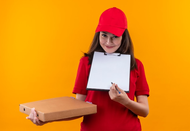 Glimlachende jonge leveringsvrouw die rode t-shirt in rode glb dragen die pizzadoos en klembord op geïsoleerde oranje muur houden
