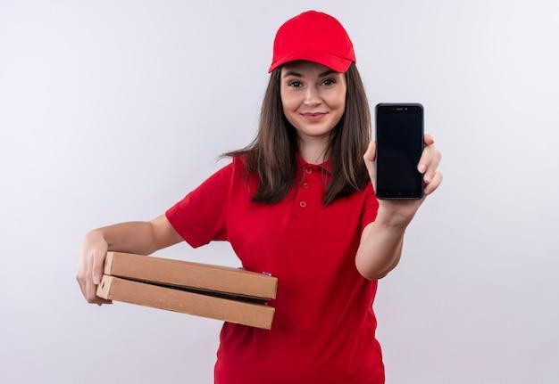 Glimlachende jonge leveringsvrouw die rode t-shirt in rode glb dragen die pizzadoos en telefoon op geïsoleerde witte muur houden
