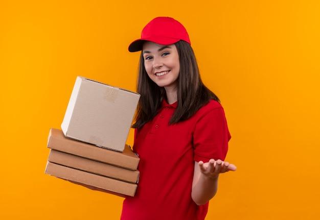 Glimlachende jonge leveringsvrouw die rode t-shirt in rode pet draagt die een doos en een pizzadoos op geïsoleerde oranje muur houdt