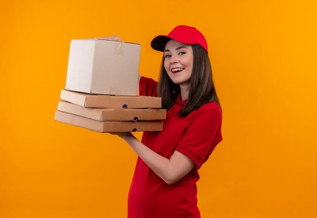 Glimlachende jonge leveringsvrouw die rode t-shirt in rode pet draagt die een doos en pizzadoos op geïsoleerde gele muur houdt