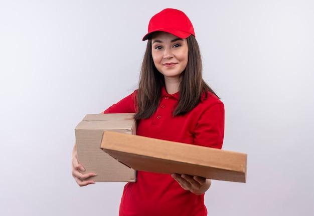 Glimlachende jonge leveringsvrouw die rode t-shirt in rode pet draagt die een doos houdt en de pizzadoos op geïsoleerde witte muur houdt