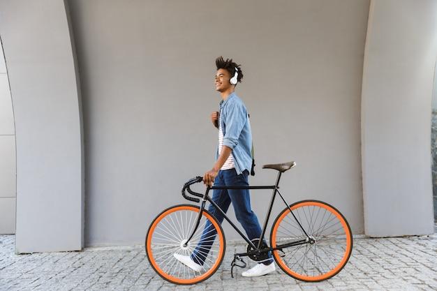 Glimlachende jonge man buitenshuis, wandelen met de fiets
