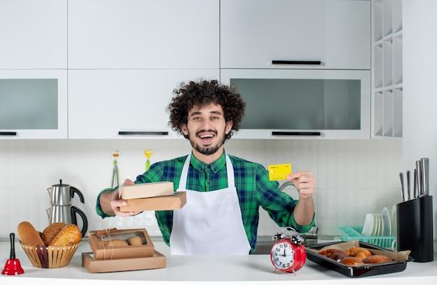 Glimlachende jonge man die achter de tafel staat met verschillende gebakjes erop en bruine bankkaartdozen vasthoudt in de witte keuken