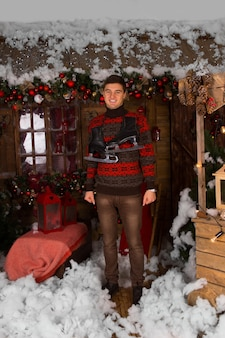 Glimlachende jonge man die bij het huis staat met veel kerstdecors in wintermode-outfit, met schaatsen om zijn nek, terwijl hij naar de camera kijkt.