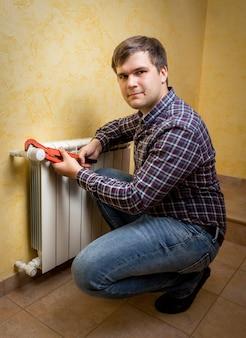 Glimlachende jonge man die een tang vasthoudt en een radiatorkraan installeert