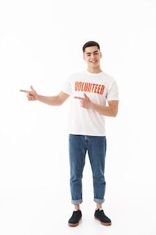 Glimlachende jonge man die een vrijwilligerst-shirt draagt dat geïsoleerd over een witte muur staat, met de vinger naar de kopieerruimte