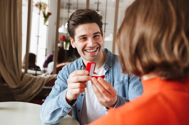 Glimlachende jonge man die een vrouw voorstelt