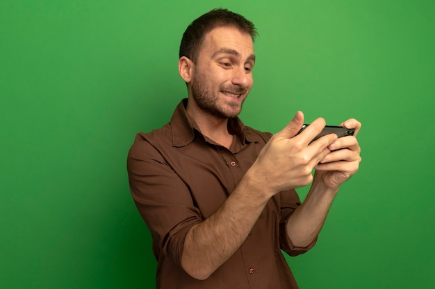 Glimlachende jonge man die en mobiele telefoon houdt bekijkt die op groene muur wordt geïsoleerd