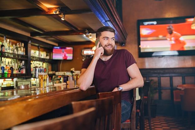 Glimlachende jonge man die in de bar zit en op mobiele telefoon praat