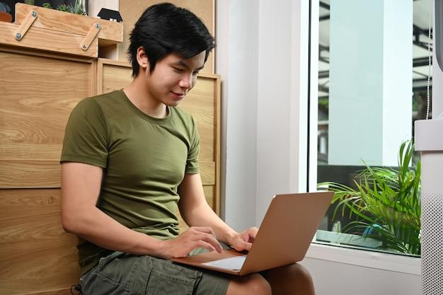 Glimlachende jonge man die in de woonkamer zit en een laptop gebruikt.