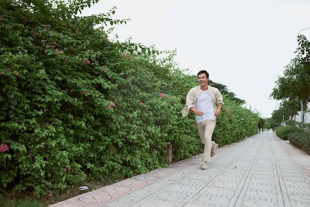 Glimlachende jonge man die in de zomer in het park loopt
