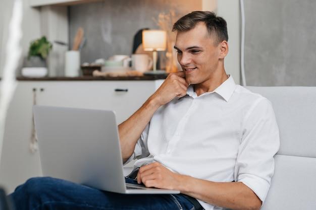 Glimlachende jonge man die naar het scherm van zijn laptop kijkt