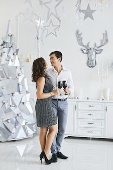 Glimlachende jonge man en mooie vrouw in modieuze jurk met wijnglazen en praten op nieuwjaar...