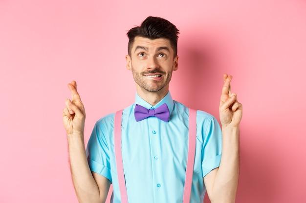 Glimlachende jonge man in vlinderdas, wens doen, bidden en opzoeken, vingers voor geluk kruisen, hoopvol permanent over roze achtergrond. kopieer ruimte