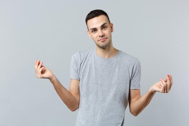 Glimlachende jonge man in vrijetijdskleding die vingers wrijft, contant gebaar toont, om geld vraagt