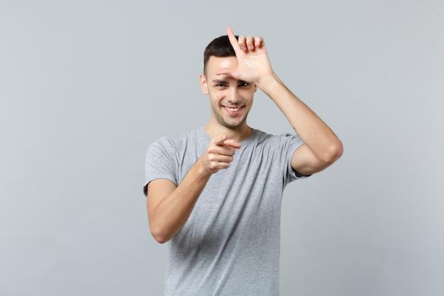 Glimlachende jonge man in vrijetijdskleding met verliezersgebaar, wijsvinger naar voren wijzend