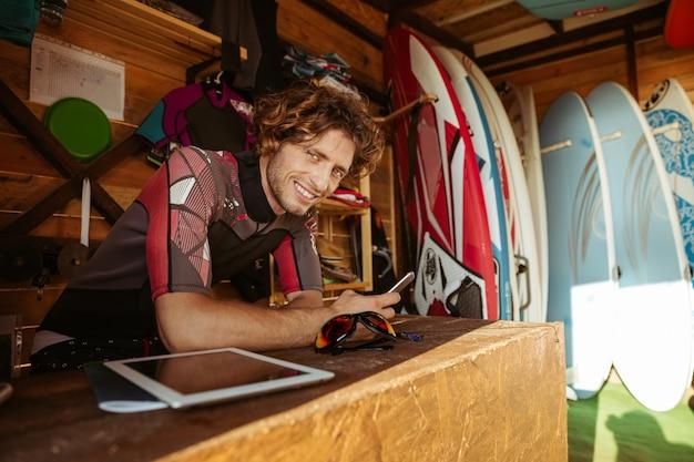 Glimlachende jonge man in zwembroek met smartphone zittend in de surf shack