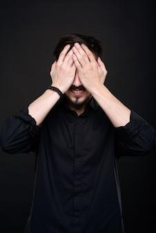 Glimlachende jonge man met baard die ogen bedekt met handen in afwachting van verrassing tegen zwarte achtergrond