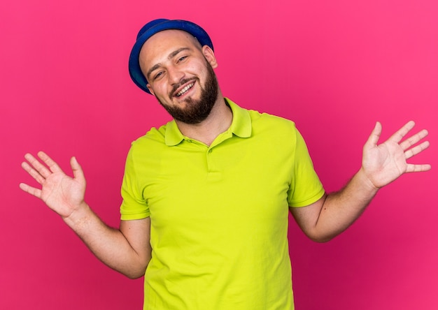 Glimlachende jonge man met blauwe feestmuts die handen uitspreidt die op roze muur worden geïsoleerd