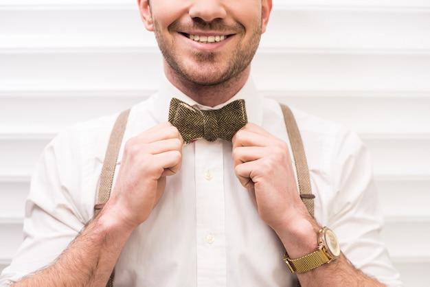Glimlachende jonge man met bretels en strikje.
