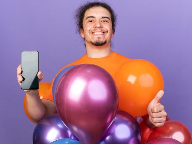 Glimlachende jonge man met een oranje t-shirt die achter ballonnen staat en een telefoon vasthoudt met duim omhoog geïsoleerd op een paarse muur