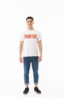 Glimlachende jonge man met een vrijwilligerst-shirt dat geïsoleerd staat over een witte muur