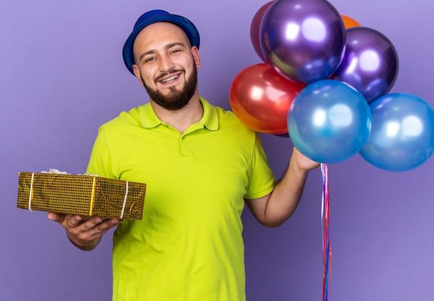 Glimlachende jonge man met feestmuts met ballonnen met geschenkdoos