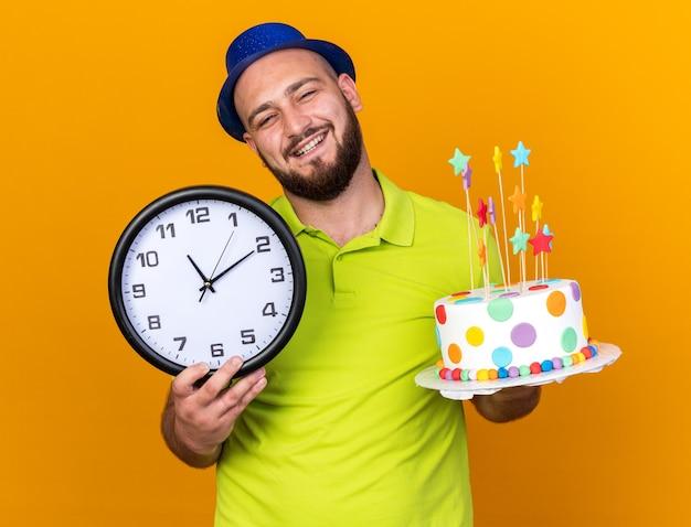 Glimlachende jonge man met feestmuts met wandklok met cake geïsoleerd op oranje muur