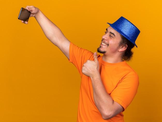 Glimlachende jonge man met feestmuts neemt een selfie met duim omhoog geïsoleerd op een oranje muur