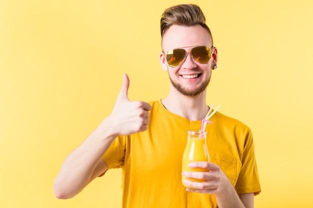 Glimlachende jonge man met fles verse smoothie. duim omhoog. gezonde biologische detox fruitdrank. zomerse verfrissing.