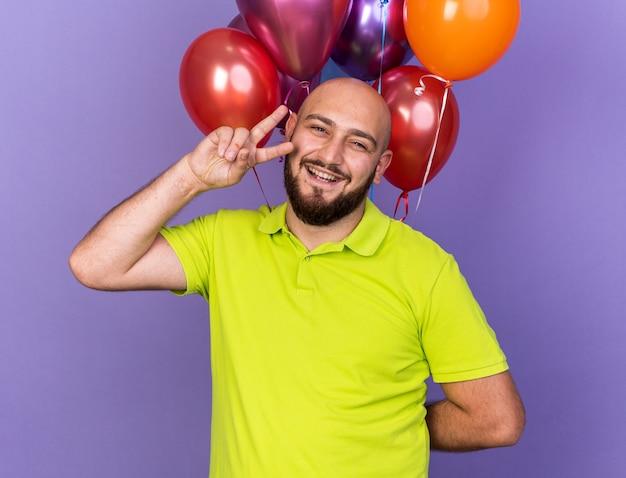 Glimlachende jonge man met geel t-shirt die vooraan staat met ballonnen die vredesgebaar tonen