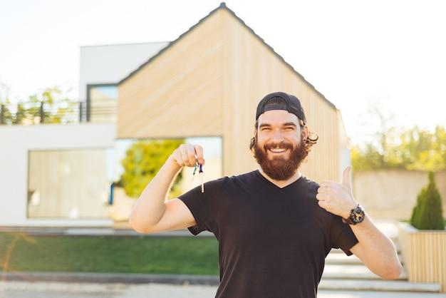 Glimlachende jonge man met huissleutels en duim opdagen