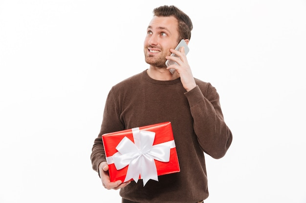 Glimlachende jonge man praten via de telefoon.