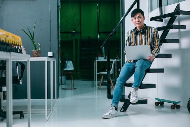 Glimlachende jonge man zittend op de zwarte trap in een wit kantoor en met een moderne laptop