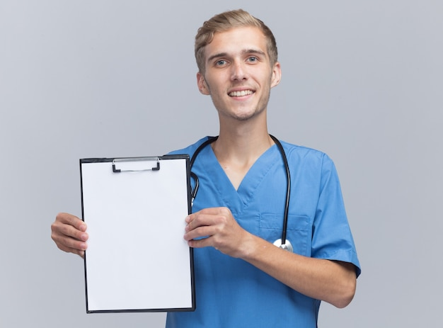 Glimlachende jonge mannelijke arts die arts eenvormig met het klembord van de stethoscoopholding draagt dat op witte muur wordt geïsoleerd