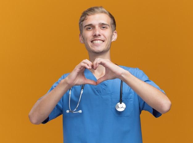 Glimlachende jonge mannelijke arts die arts eenvormig met stethoscoop draagt die hartgebaar toont dat op oranje muur wordt geïsoleerd