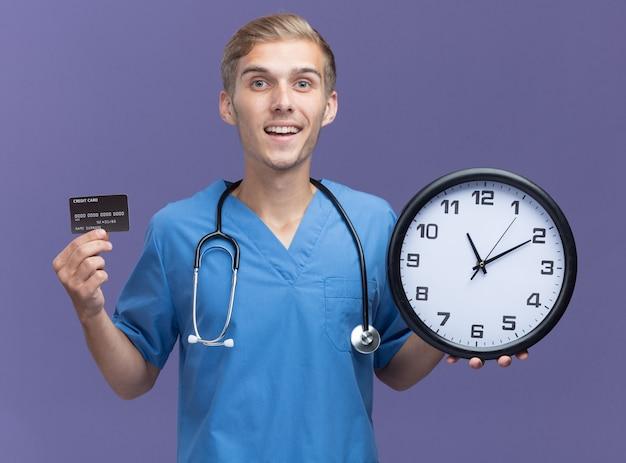Glimlachende jonge mannelijke arts die artsenuniform met de creditcard van de stethoscoopholding met muurklok draagt die op blauwe muur wordt geïsoleerd