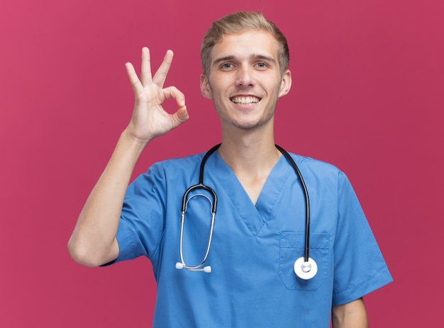 Glimlachende jonge mannelijke arts die artsenuniform met stethoscoop draagt die ok gebaar tonen dat op roze muur wordt geïsoleerd