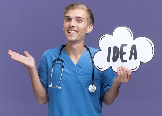 Glimlachende jonge mannelijke arts die doktersuniform draagt met een stethoscoop met een ideebel die de hand verspreidt, geïsoleerd op een blauwe muur