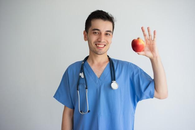 Glimlachende jonge mannelijke arts die en appel tonen aanbevelen.