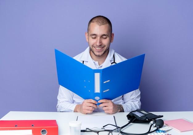 Glimlachende jonge mannelijke arts die medische mantel en stethoscoop draagt die aan bureau met uitrustingsstukken houdt en map bekijkt die op purpere muur wordt geïsoleerd