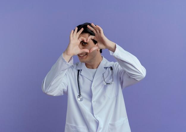 Glimlachende jonge mannelijke arts die medische mantel en stethoscoop draagt die hartteken doen die erdoorheen kijken geïsoleerd