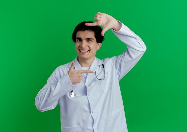 Glimlachende jonge mannelijke arts die medische mantel en stethoscoop draagt die kadergebaar doet dat op groene muur met exemplaarruimte wordt geïsoleerd