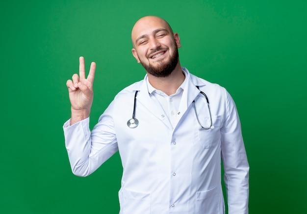 Glimlachende jonge mannelijke arts die medische mantel en stethoscoop draagt die okgebaar toont dat op groen wordt geïsoleerd