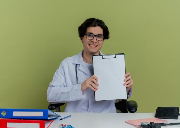 Glimlachende jonge mannelijke arts die medische mantel en stethoscoop met glazen draagt die aan bureau met medische hulpmiddelen zitten die geïsoleerd tonen klembord kijken