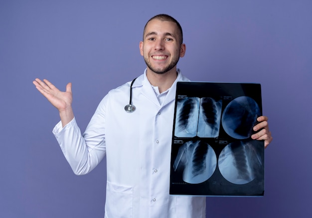 Glimlachende jonge mannelijke arts die medische mantel en stethoscoop om zijn nek draagt die röntgenfoto houdt en lege hand toont die op purpere muur wordt geïsoleerd