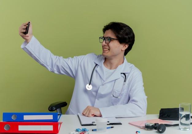 Glimlachende jonge mannelijke arts die medische robe en stethoscoop met glazen draagt die aan bureau zitten
