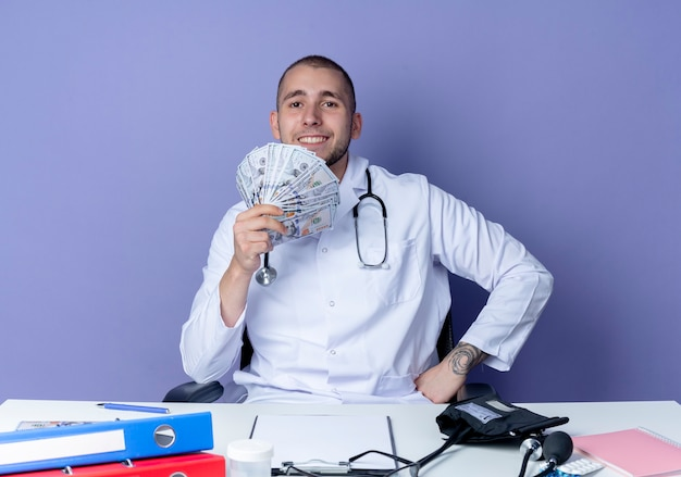 Glimlachende jonge mannelijke arts die medische robe en stethoscoopzitting aan bureau met uitrustingsstukken draagt die geld met hand op taille houden die op purpere muur wordt geïsoleerd